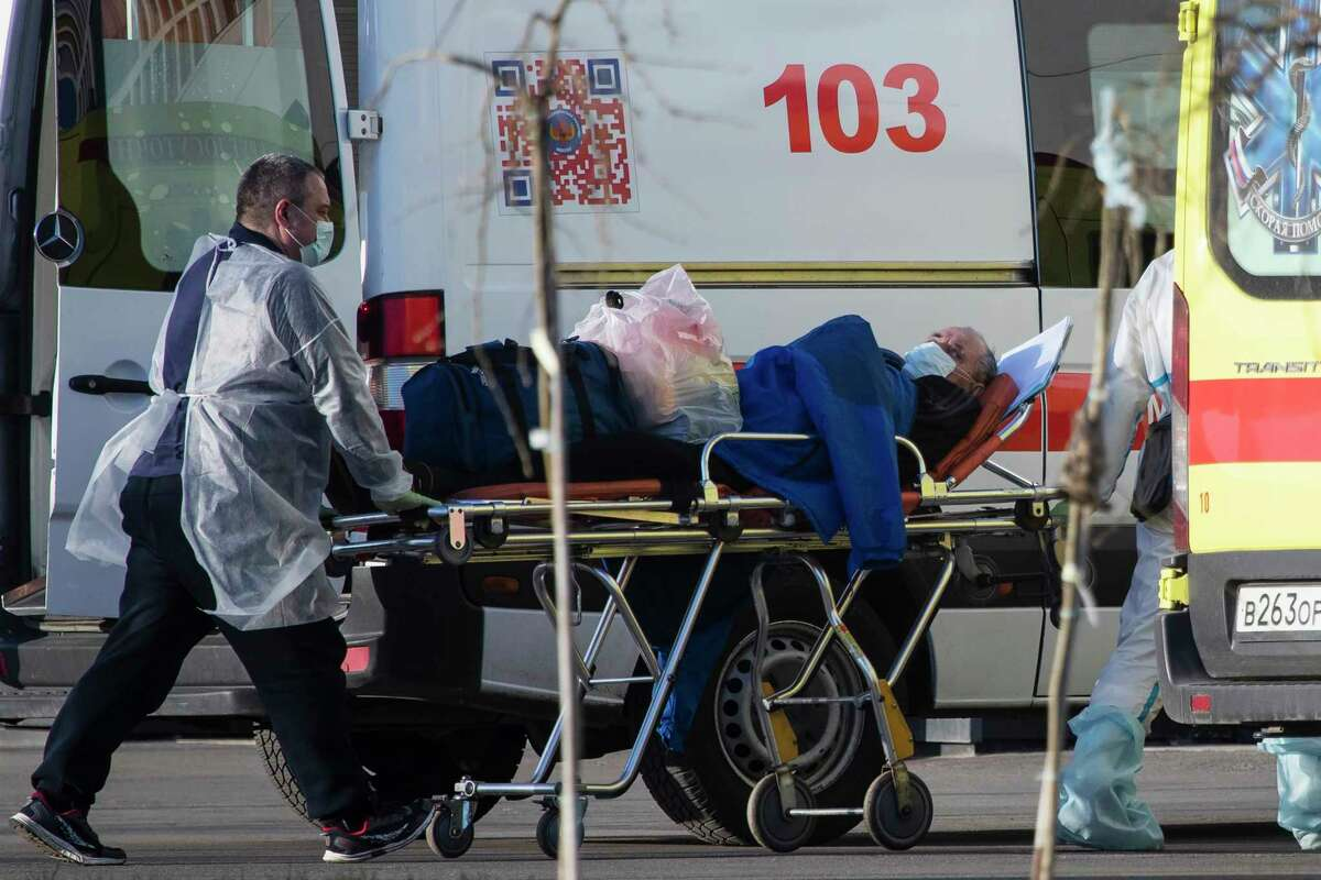 Medical workers wearing protective gear carry on a stretcher a man, suspected of having the coronavirus infection, at a hospital in Kommunarka, outside Moscow, Russia, Wednesday, April 29, 2020.