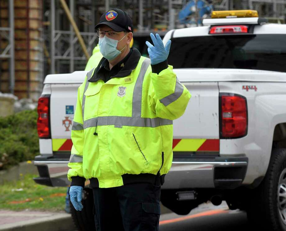 A Stamford police officer directs traffic while wearing a mask and gloves along Washington Blvd. on April 8, 2020 in Stamford, Connecticut. The city is testing all police officers and other first responders for coronavirus, whether they are showing symptoms or not. Photo: Matthew Brown / Hearst Connecticut Media / Stamford Advocate
