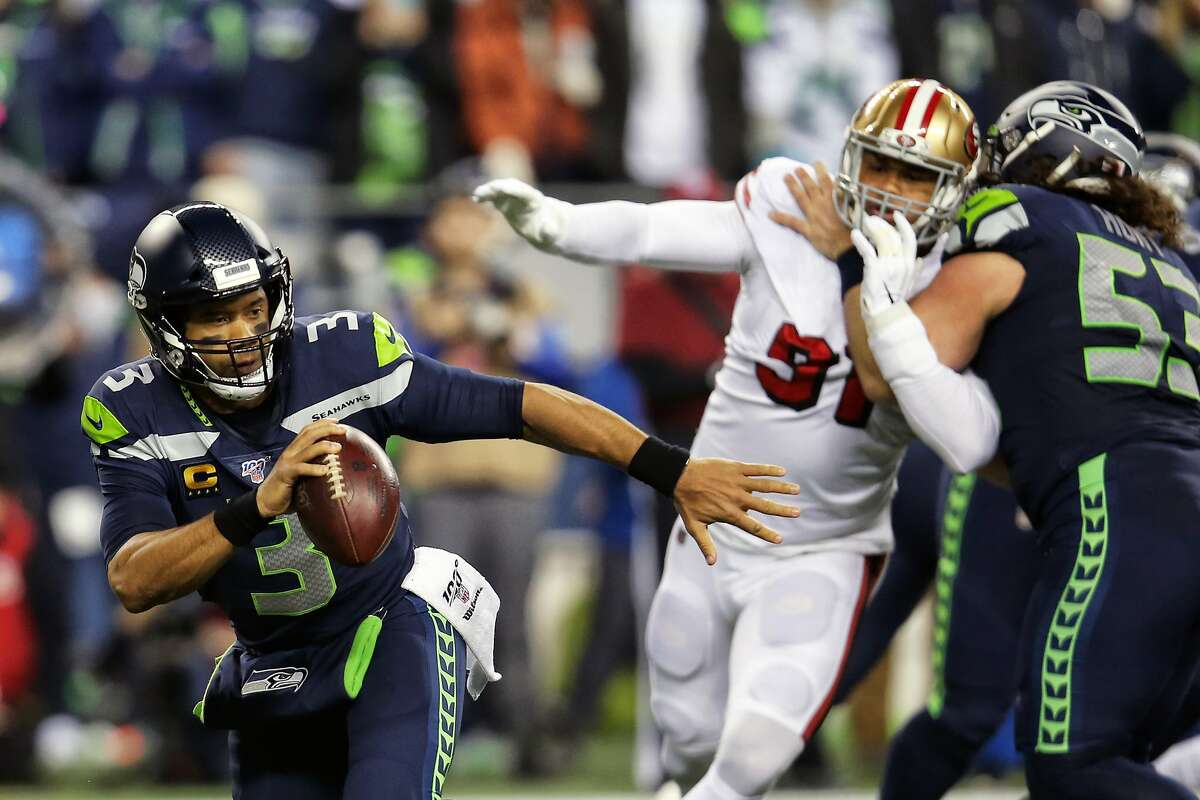 Seattle Seahawks quarterback Russell Wilson (3) scrambles away from the defense in the first half of Seattle's game against San Francisco, Sunday, Dec. 29, 2019 at CenturyLink Field. (Genna Martin, Seattlepi.com)