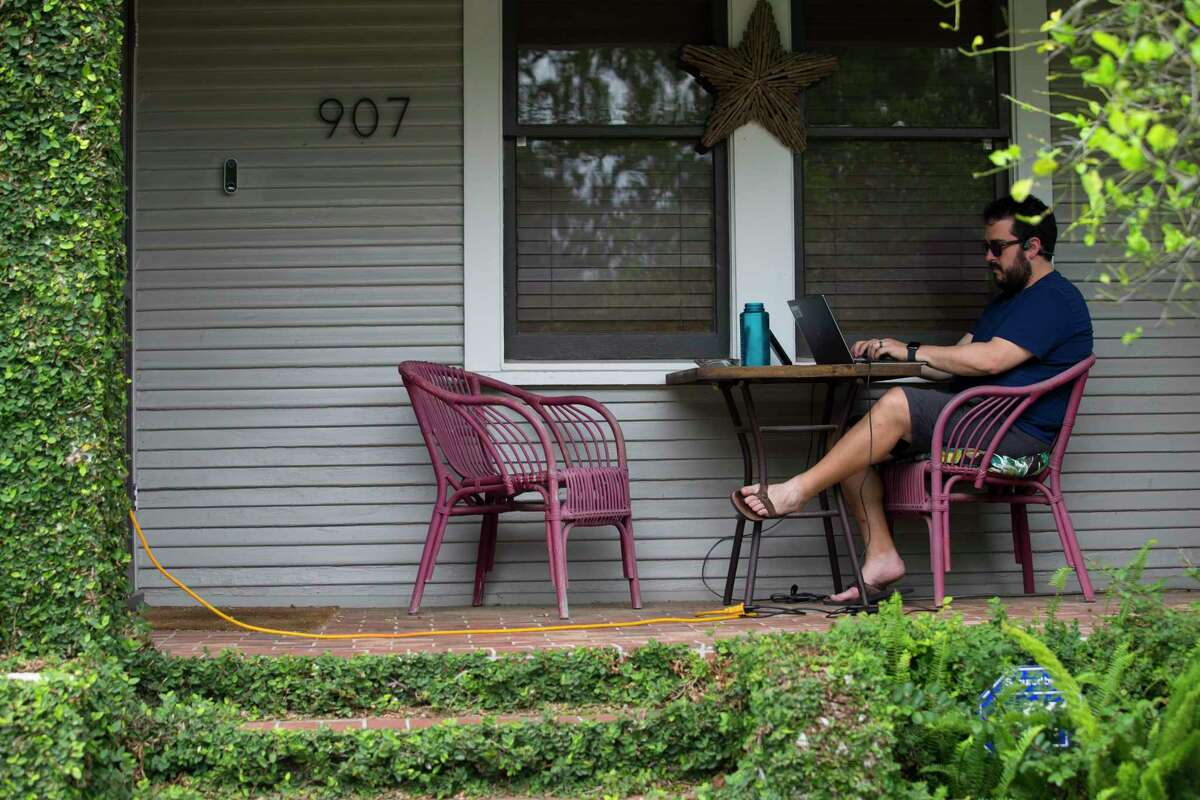 Eric Grzelak works from his porch in the Norhill neighborhood of Houston on April 7, 2020.
