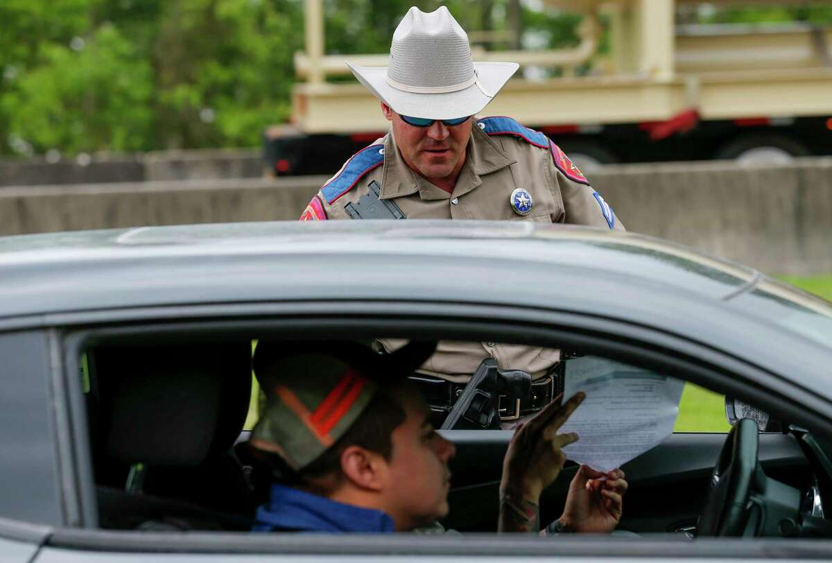 A Texas Highway Patrol trooper talks to a motorists who stopped to ask a question at the Texas Travel Information Center parking lot Monday, March 30, 2020, in Orange, Texas. Gov. Greg Abbott on Sunday tightened travel to Texas, ordering some motorists from Louisiana to self-quarantine for two weeks. The new restrictions were effective Monday at noon, and DPS said they will not be establishing checkpoints at this time.