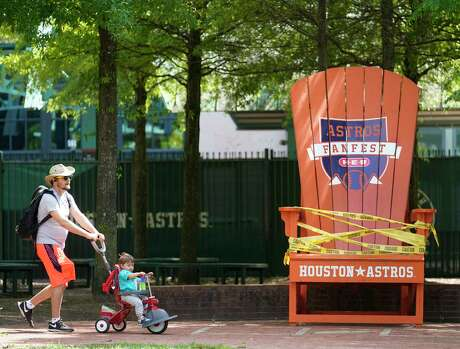 Daniel Estebanez pushes his 19-month-old son, Lucas Estebanez, by the cordoned off giant Houston Astros chair in the Plaza at Minute Maid Park Wednesday, April 29, 2020, in Houston. Major League Baseball delayed the start of the season amid the Covid-19 pandemic.