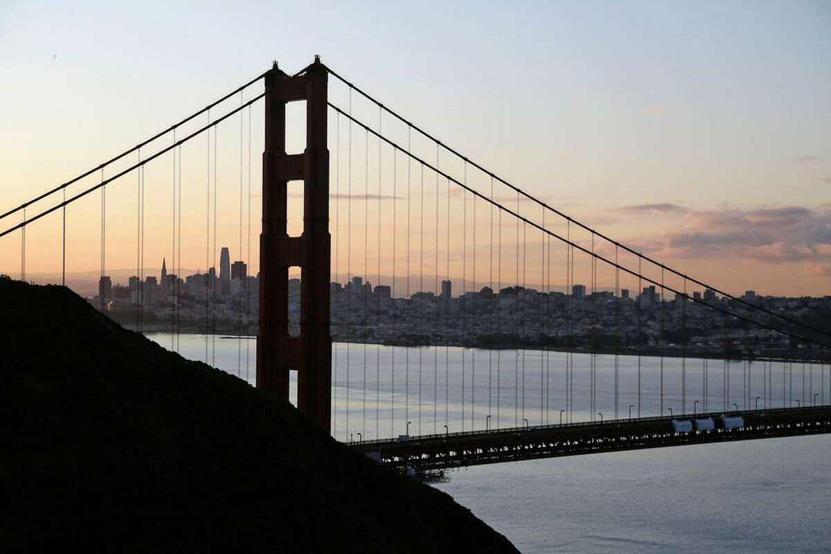 """The San Francisco skyline is seen shortly after sunrise behind the Golden Gate Bridge Tuesday, March 17, 2020, in Sausalito, Calif. About 7 million people in the San Francisco Bay Area woke up Tuesday to nearly empty highways, shuttered stores and vacant streets after officials issued an order for residents to shelter at their homes and only leave for """"essential"""" reasons in a desperate attempt to slow the spread of the coronavirus."""