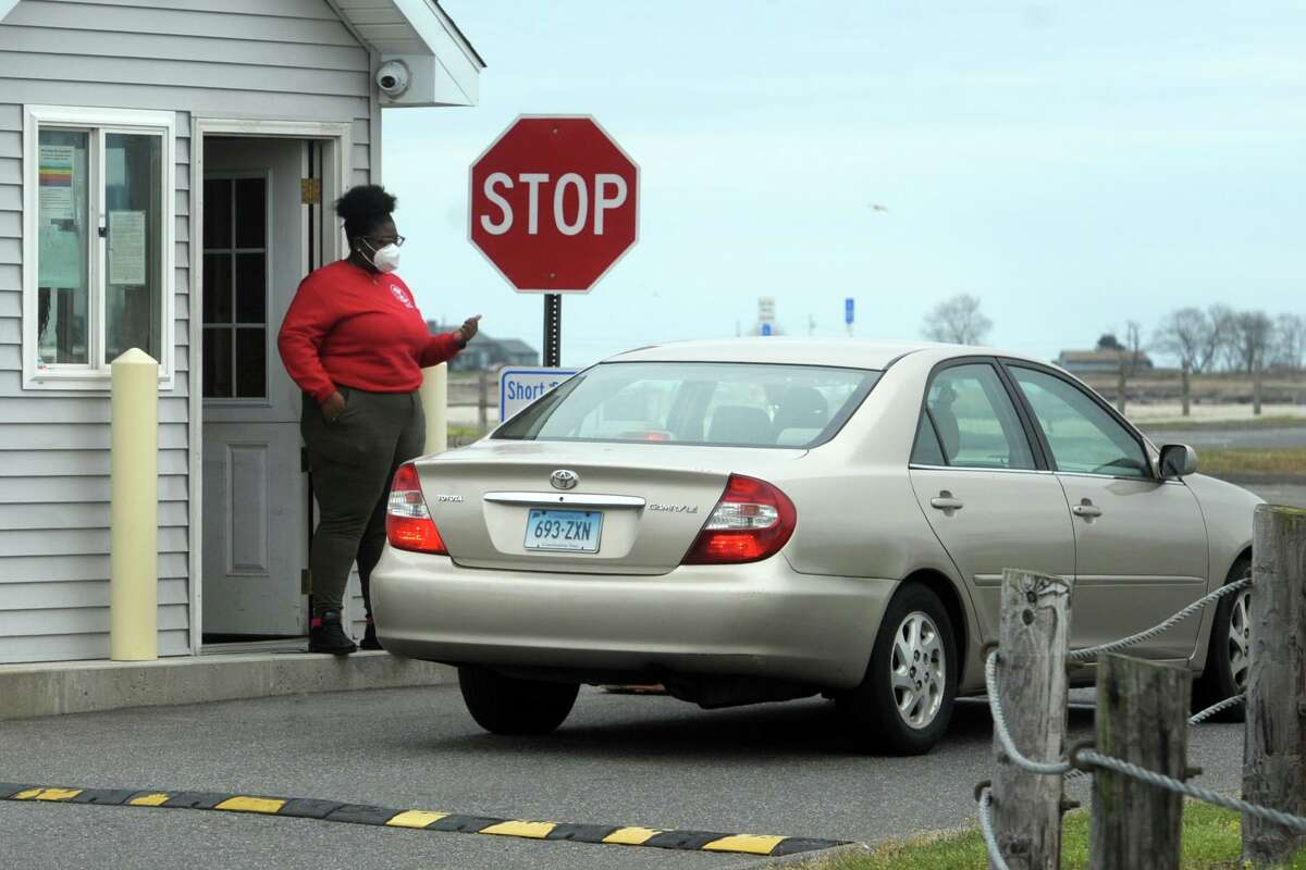 A woman checks for town stickers at the entrance to Short Beach, in Stratford, Conn. April 29, 2020. Stratford beaches and shoreline access have remained open to town residents during the pandemic.