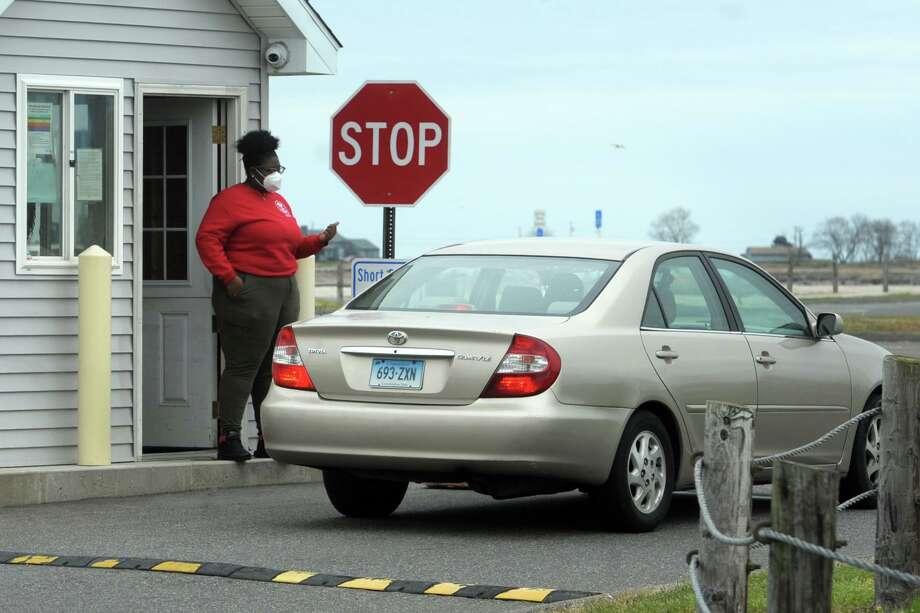 A woman checks for town stickers at the entrance to Short Beach, in Stratford, Conn. April 29, 2020. Stratford beaches and shoreline access have remained open to town residents during the pandemic. Photo: Ned Gerard / Hearst Connecticut Media / Connecticut Post