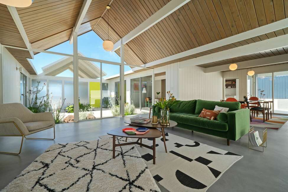 The living room is mid-century and contemporary: those angles and beamed ceilings meet lighter colored walls and floors, creating light in the space. Note that there are no posts or horizontal beams in the middle of the
