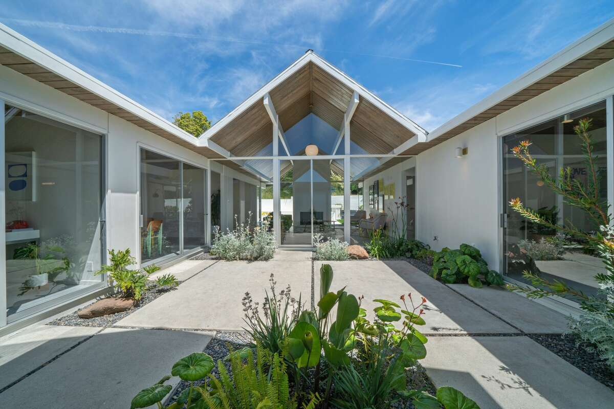 Many Eichlers are built around courtyards or atriums, and this one is no different, with separate wings of the house facing this central open space though glass walls.