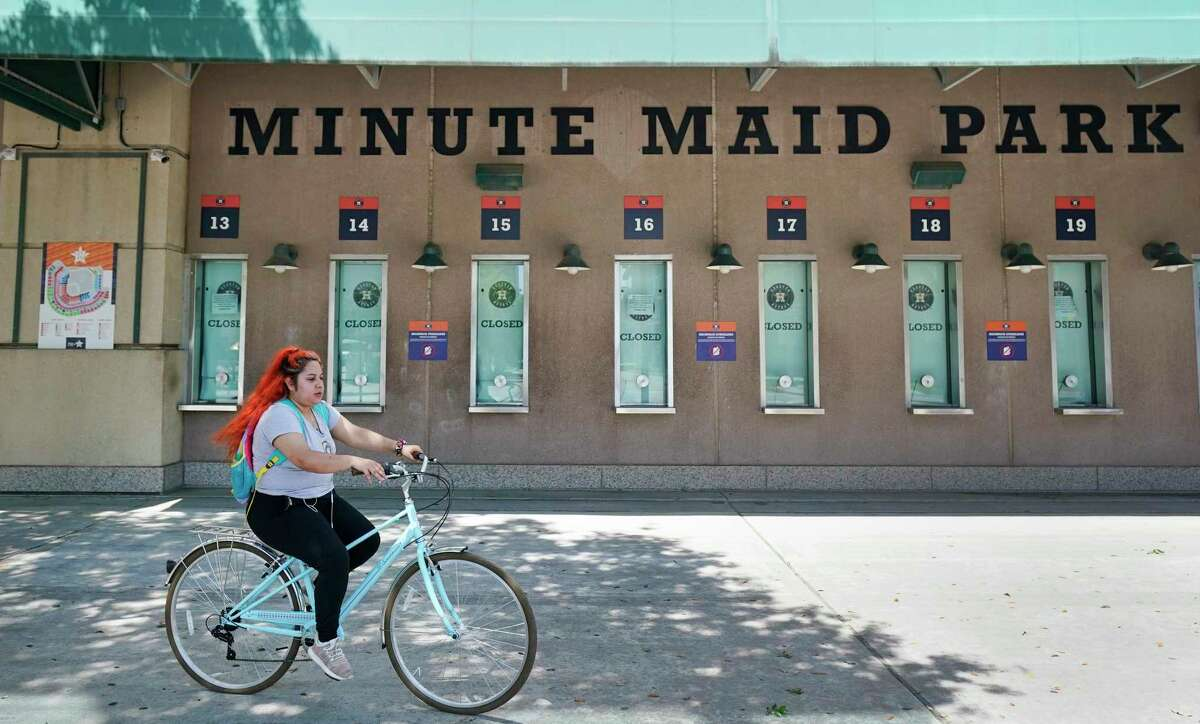 A bicyclist rides by the closed Houston Astros ticket windows at Minute Maid Park is shown Wednesday, April 29, 2020, in Houston. Major League Baseball delayed the start of the season amid the Covid-19 pandemic.