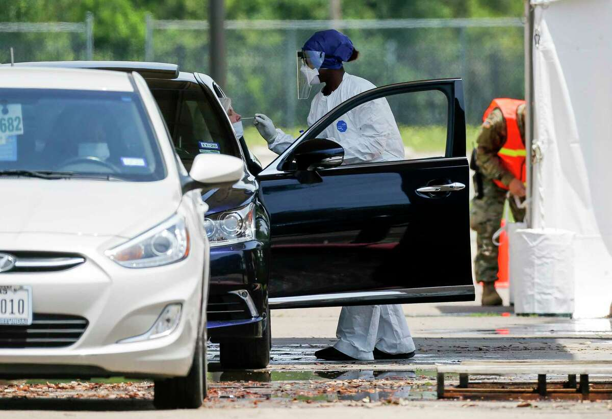 A health professional conducts a COVID-19 test on a motorist at Worthing High School on Wednesday.