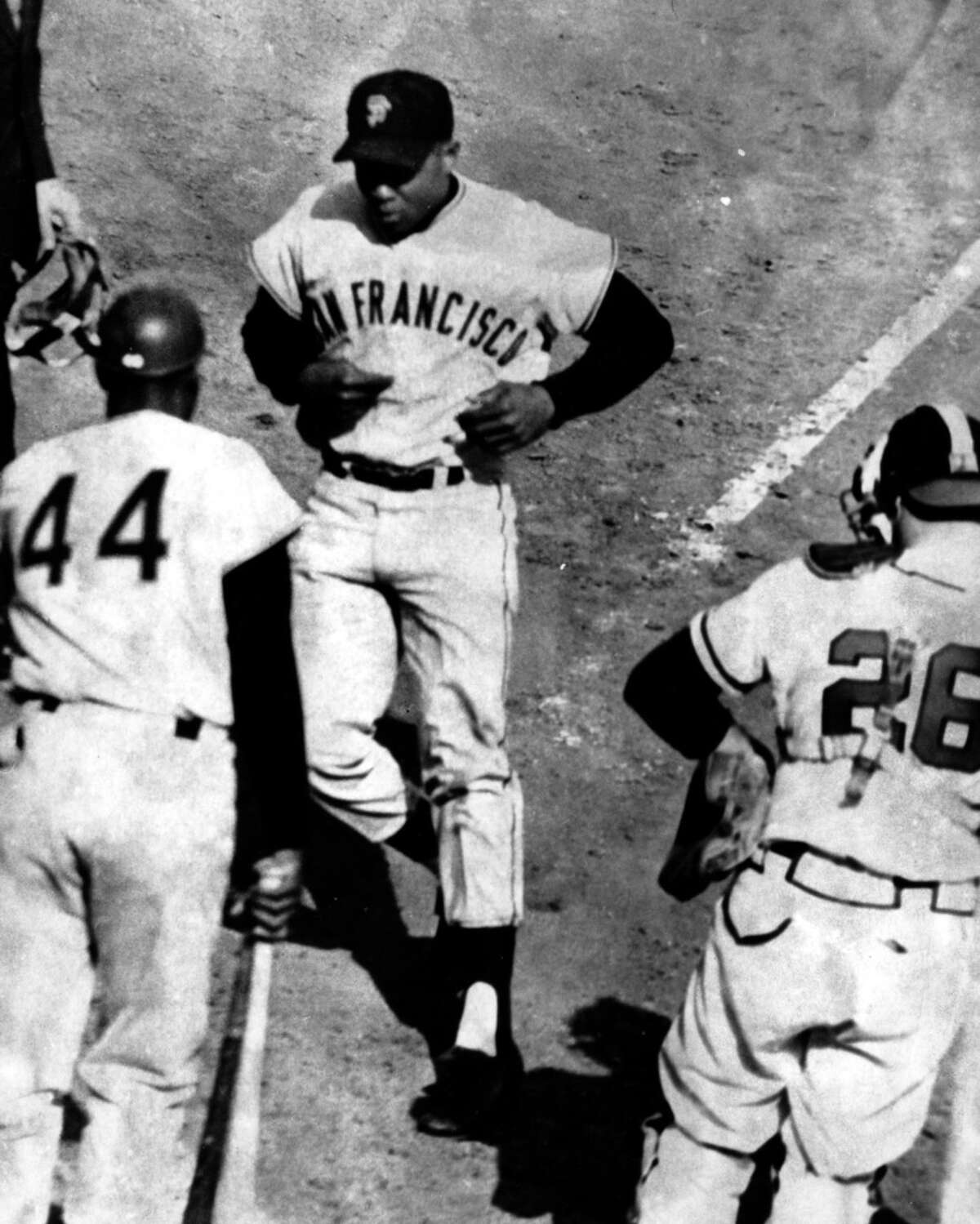 Willie Mays, center, jogs toward home plate after his fourth homer in the eighth inning against the Braves on April 30, 1961 in Milwaukee. Willie McCovey, left, and Braves catcher Hawk Taylor, right, watch the run score.