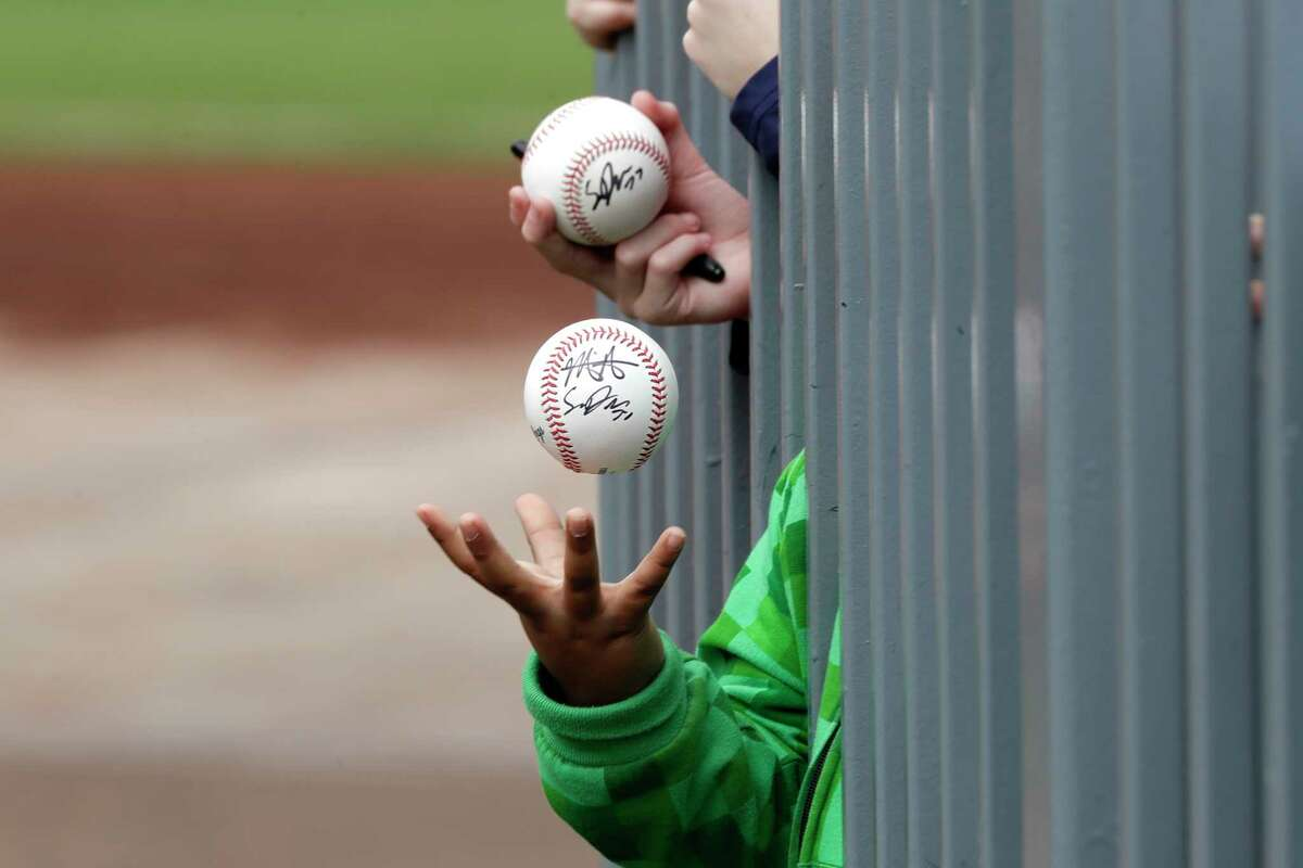 FILE - In this March 10, 2020, file photo, a child tosses an already-autographed baseball while awaiting another signature from a passing player before a spring training baseball game between the Los Angeles Angels and the Seattle Mariners in Peoria, Ariz. Doctors, scientists and sports leaders are outlining the path back to playing fields for children in grassroots sports -- an exercise that could inform major organizations on how to get their industries up and running as well in the midst of the COVID-19 pandemic. (AP Photo/Elaine Thompson, File)