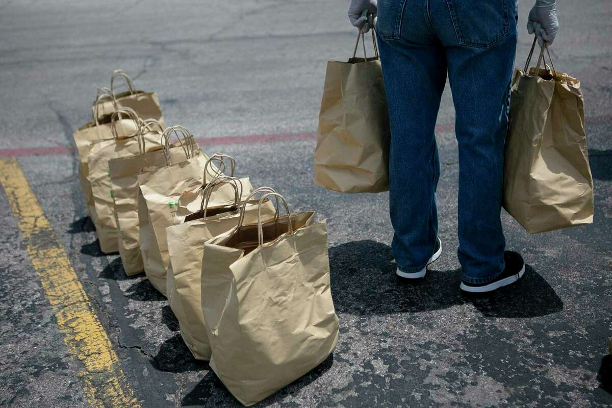 A volunteer carries bags of produce to give out during the Lots of Love and the San Antonio Food Bank food distribution event at Pica Pica Plaza in San Antonio, Texas on April 29, 2020.