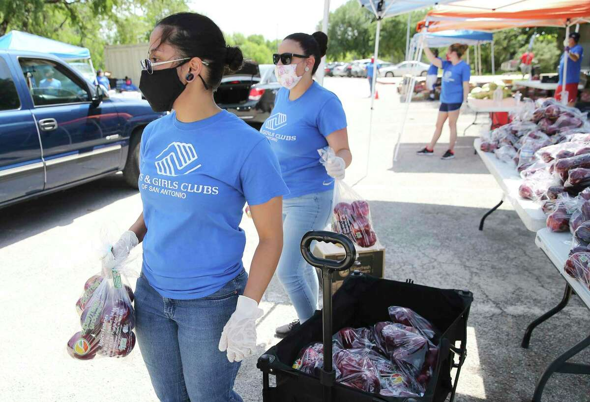 Chelsea Colton (front) and Amber Gonzalez ready bags of apples to place into vehicles as the Boys and Girls Clubs of San Antonio host a food distribution in the city's Eastside Community for about 300 families at Martin Luther King Park on Wednesday, Apr. 29, 2020. Spokeswoman and Chief of Development Renee Garvens said the organization has been distributing food since the third week of March. They have also been providing pre-packaged meals for school kids. On Wednesday, cars lined up early as staffers organized produce brought in by the San Antonio Food Bank. At 3 p.m. the first car came through as items like apples, cabbage, potatoes and a box of assorted vegetables were placed into the vehicles. To date, Boys and Girls Club of San Antonio has provided 3,599 families with emergency food according to Garvens.