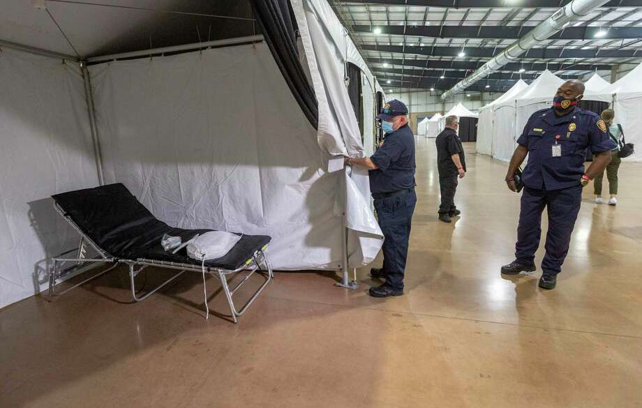 San Antonio Fire Department chief Charles Hood, right, looks Wednesday at one of the beds in the alternate care facility that has been built inside the Expo Hall on the grounds of the AT&T Center and Freeman Coliseum. The facility, which currently has 80 beds but could expand, was built to provide extra bed space for people with medical needs if area hospitals were overwhelmed with COVID-19 patients. But it hasn't been needed. Photo: William Luther /Staff / ©2020 San Antonio Express-News