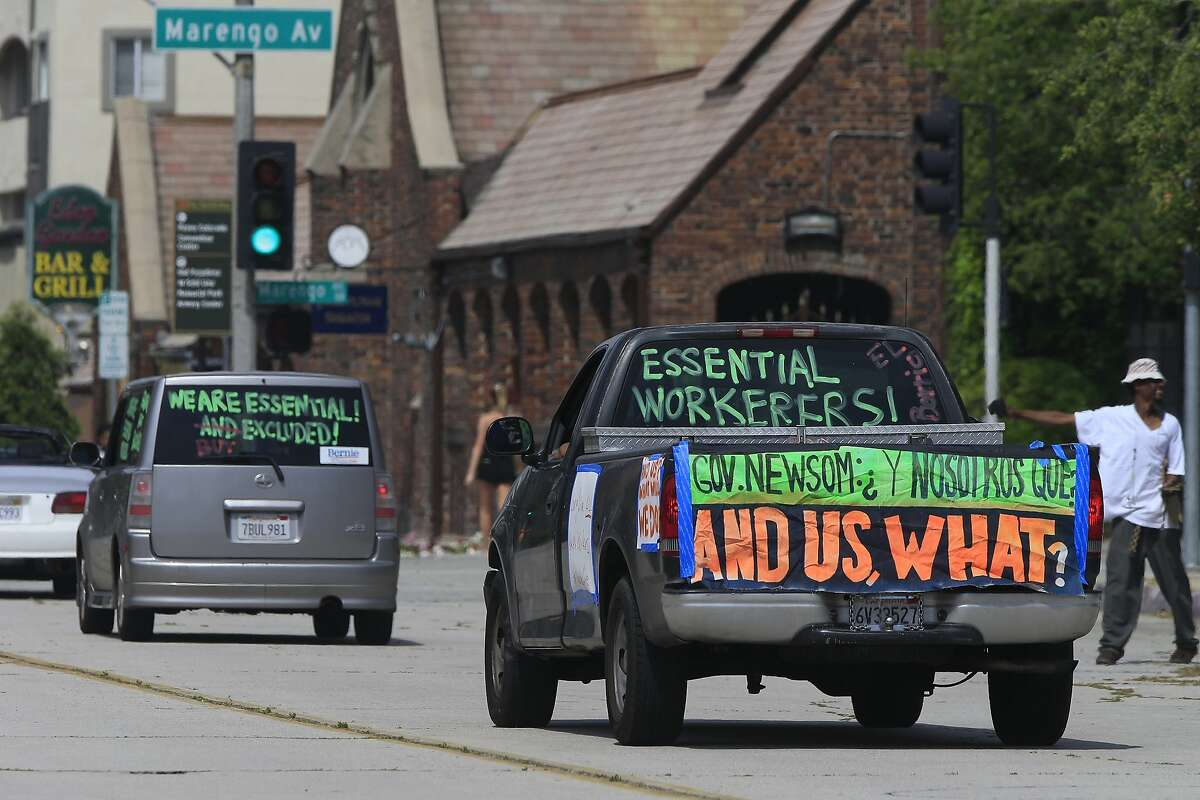 """Pasadena day laborers and supporters hold a """"COVID-19-safe car rally"""" to protest what they say is an exclusion of workers from financial protection in the wake of the current pandemic for essential immigrant workers outside the city hall in Pasadena, Calif., Wednesday, April 29, 2020. A surge in unemployment caused by the coronavirus shutdown has started to take a financial toll on state jobless funds. At least six states have already asked to borrow money from the federal government to pay unemployment claims because their state funds are expected to run out. (AP Photo/Damian Dovarganes)"""