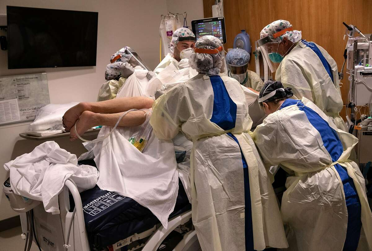 """STAMFORD, CONNECTICUT - APRIL 24: A """"prone team,"""" wearing personal protective equipment (PPE), turns a COVID-19 patient onto his stomach in a Stamford Hospital intensive care unit (ICU), on April 24, 2020 in Stamford, Connecticut. The civilian/military team, made up of physical and occupational therapists turns over COVID-19 patients to help their labored breathing and increase lung capacity. Stamford Hospital, like many across the US, opened additional ICUs and have been augmented by military medical personnel to deal with the heavy patient load. Stamford, with it's close proximity to New York City, has the highest number of coronavirus patients in Connecticut. (Photo by John Moore/Getty Images)"""
