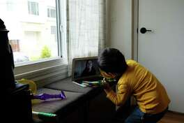 Babysitter Victoria Rodriguez from the Babysitting Company talks to a 3-year-old about his toy over a Zoom video call in San Francisco, where schools are closed during the pandemic.