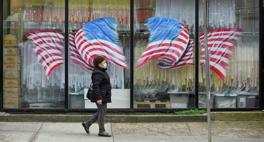 A pedestrian passes in front of American Flags displayed on the windows of Stamford Uniform in Stamford, Connecticut on April 29, 2020. Owner Paul McDonald has seen a dramatic decrease in business as a direct result of the COVID-19 pandemic. The dry cleaning laundry service provides uniform, linen towel, apron and napkin to regional clients in Connecticut and New York. Photo: Matthew Brown / Hearst Connecticut Media / Stamford Advocate