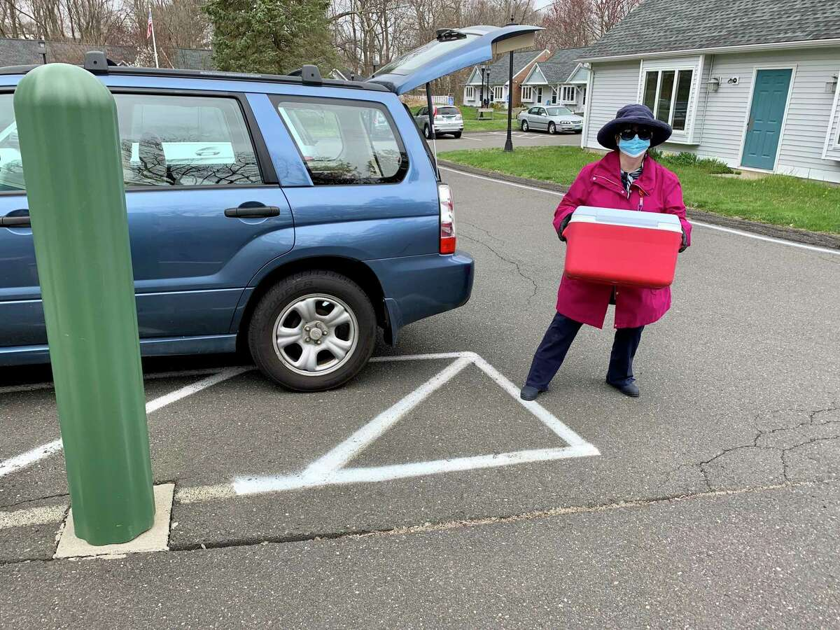 Ridgefield Meals On Wheels volunteer Lynett Dickman wears protective gear while delivering food to a client.