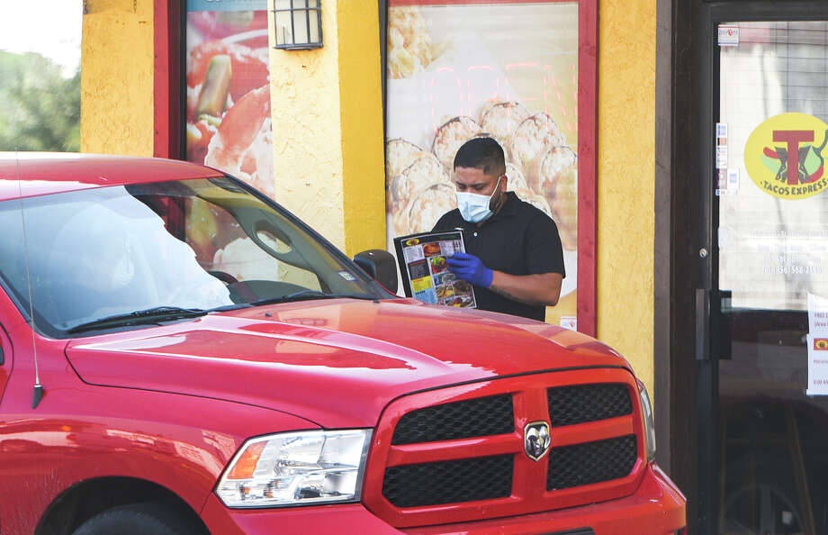 A Taco Express employee takes curbside orders, Tuesday, Apr. 28, 2020, outside Taco Express. Photo: Danny Zaragoza/Laredo Morning Times