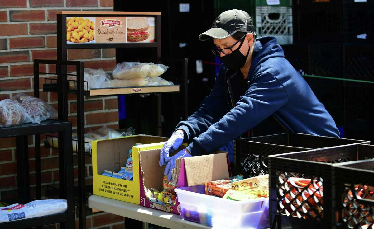 Person-to-Person staff and volunteers help clients as they receive food at their Norwalk facility Tuesday, April 28, 2020, in Norwalk, Conn.