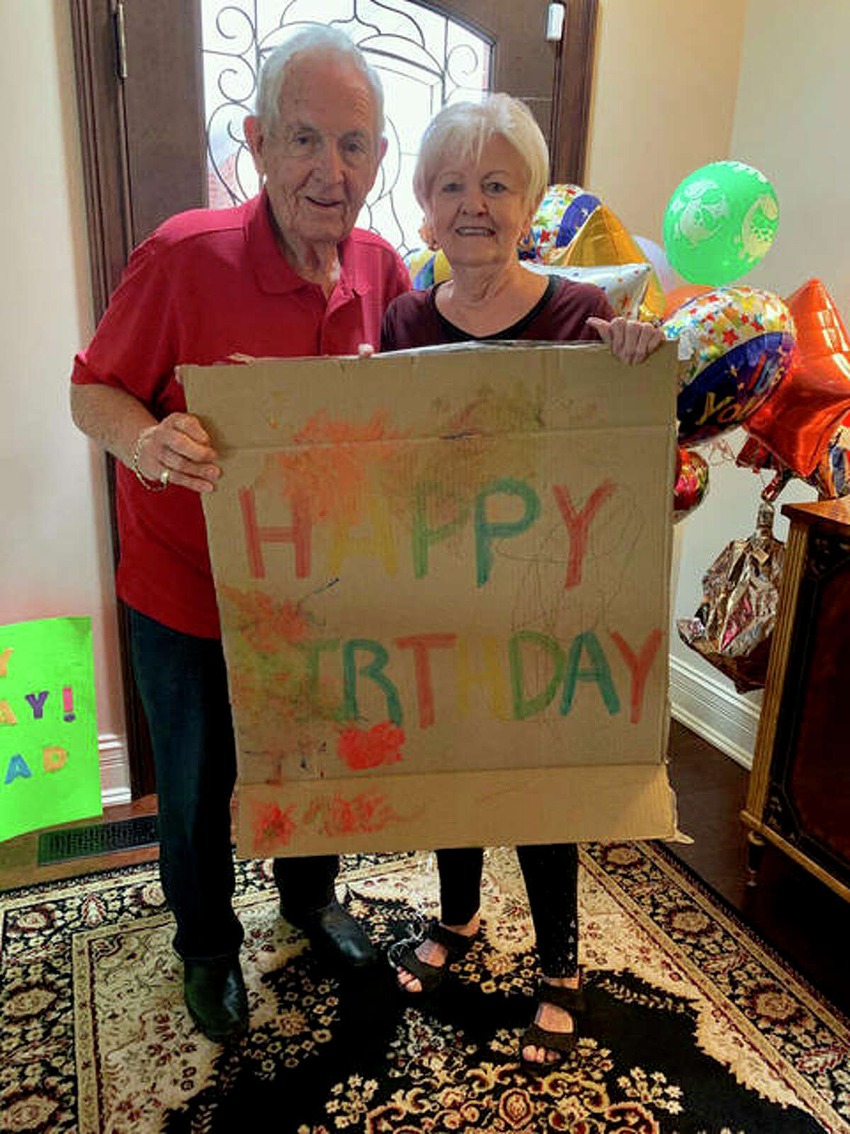 Dean and Joan Flake display some of the signs from the surprise celebration for their shared birthday on Monday. A parade of about 30 cars drove past the Traws' Edwardsville home to mark the occasion.