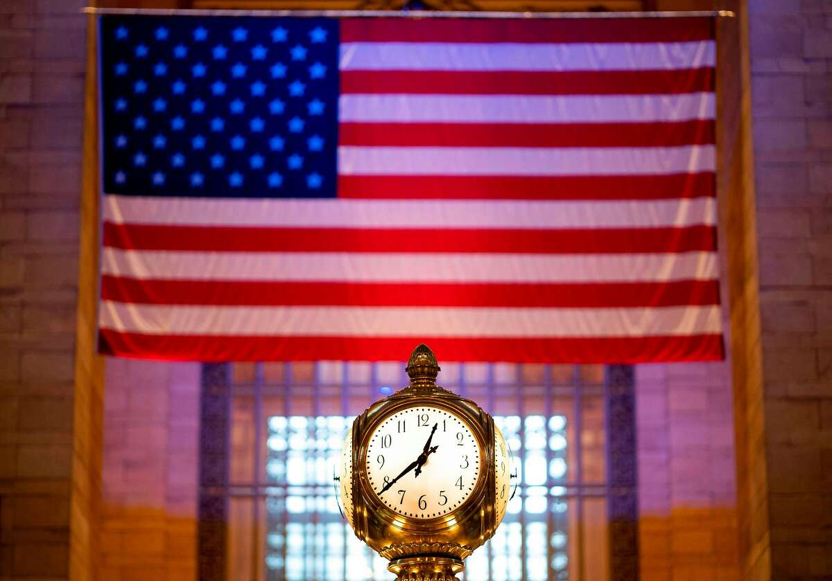 Grand Central clock is pictured in front of the American flag amid the coronavirus pandemic in Grand Central station on April 24, 2020 in New York City. - The United States recorded 1,258 coronavirus deaths on April 24, the lowest daily toll in the country in nearly three weeks, according to a tracker maintained by Johns Hopkins University. (Photo by Johannes EISELE / AFP) (Photo by JOHANNES EISELE/AFP via Getty Images)