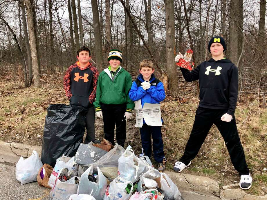 From left, Jay, 11, Brady, 10, Ryan, 8, and Tyler Streeter, 14, with the many bags of trash they collected on Earth Day. (Photo provided)
