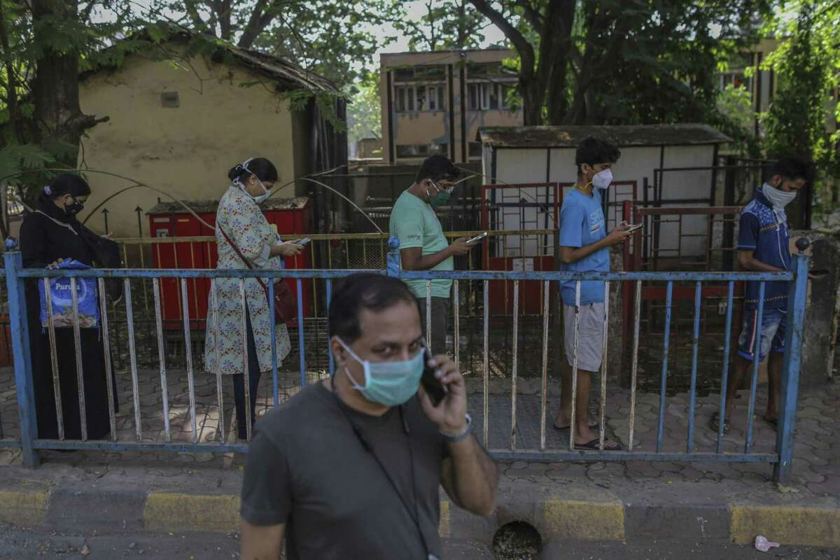 People wearing protective masks practice social distancing at a market during a lockdown imposed due to the coronavirus in Mumbai on April 5, 2020.