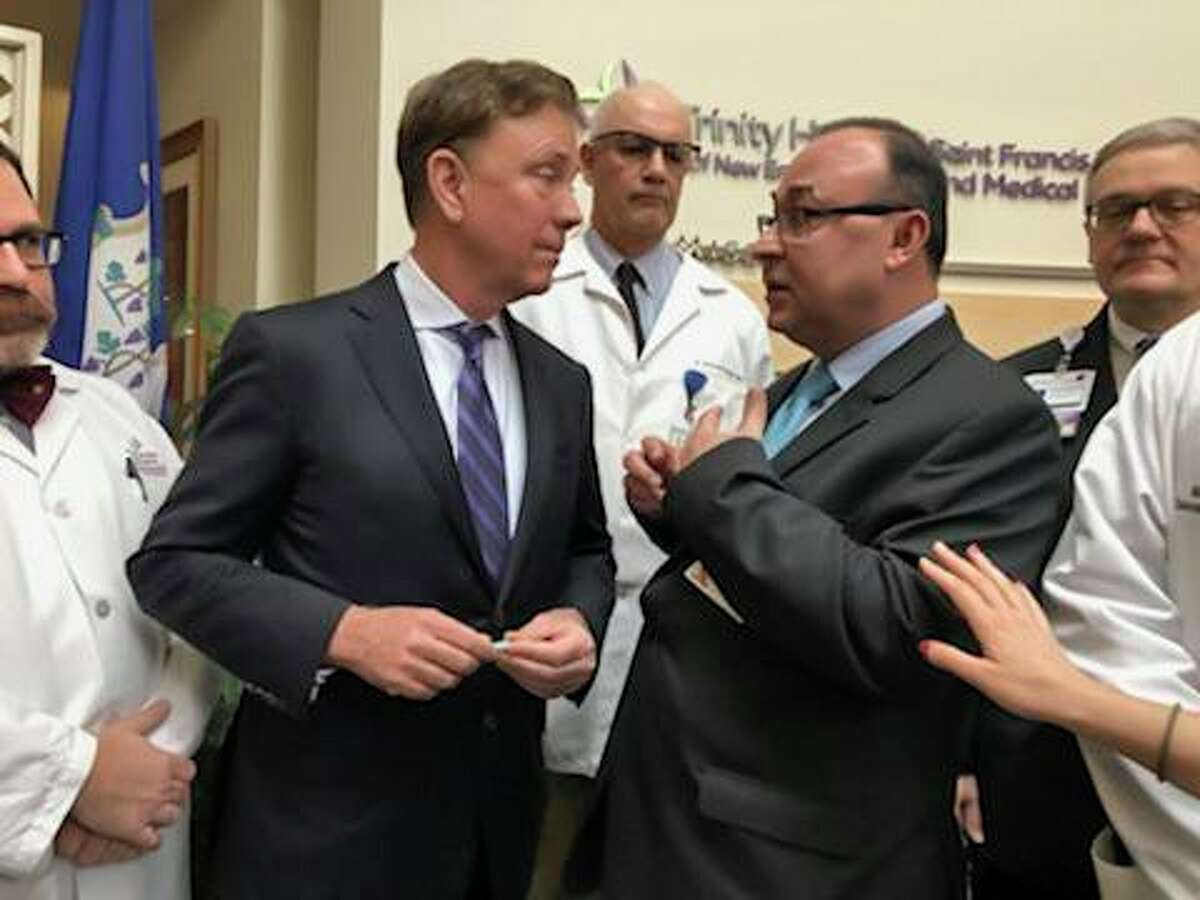 In a photo from last month, Gov. Ned Lamont, with tie on the left, listened to Dr. Danyal Ibrahim, regional chief quality officer for Trinity Health Of New England.