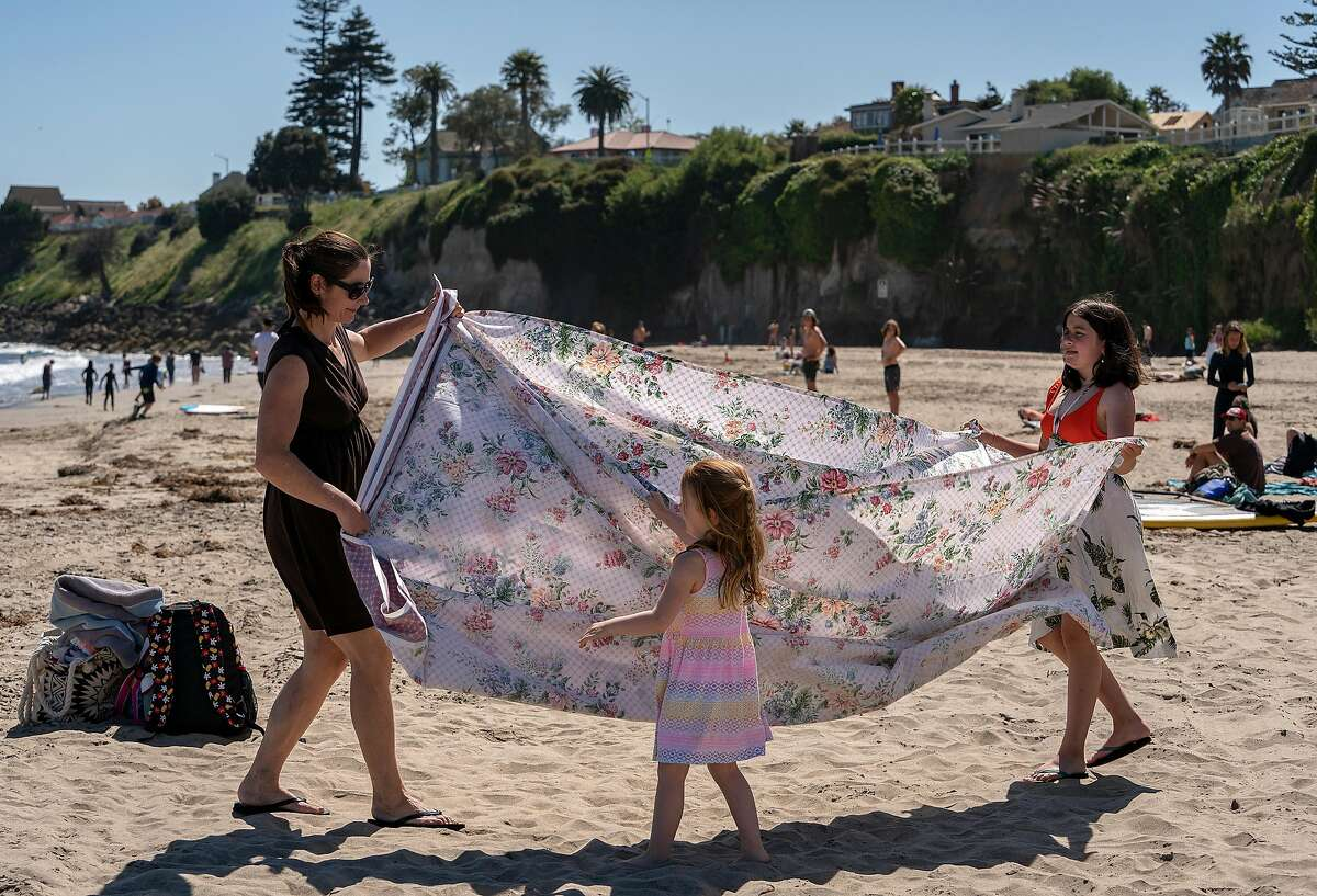 From left, Lindsey Nelson and her daughters Emma, 4, and Lucy,10, of Santa Cruz, shake the sand out of the blanket as they prepare to leave Cowell Beach on Wednesday, April 22, 2020 in Santa Cruz, Calif.