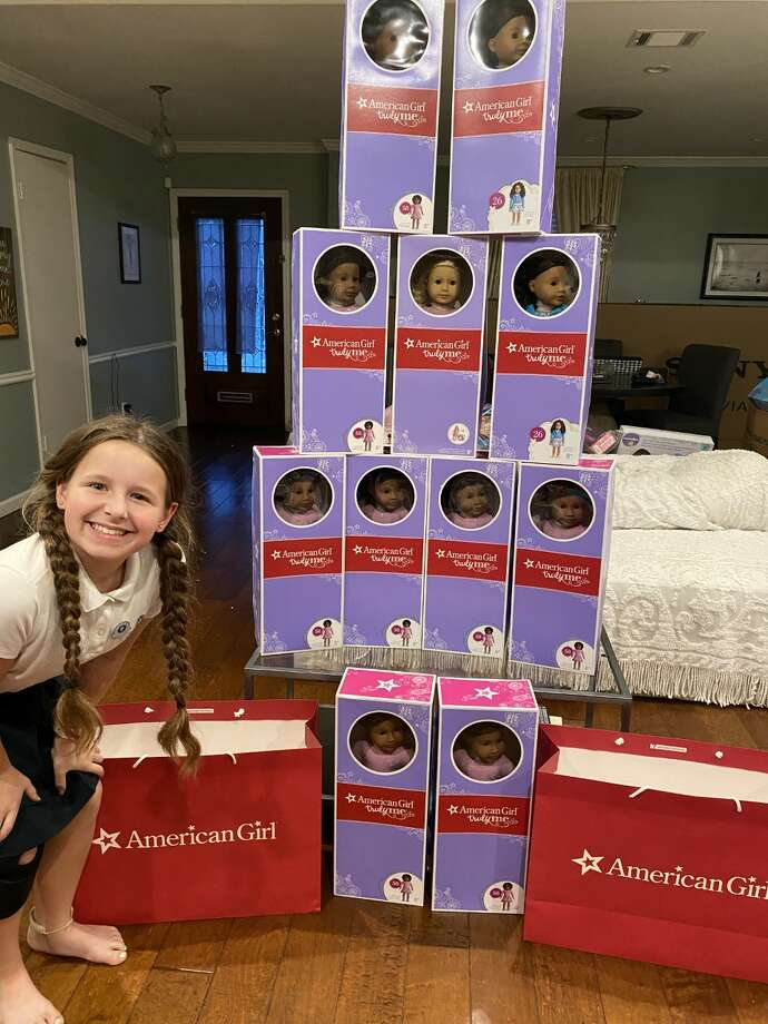 Lily is all smiles as she poses in front of a tower of American Girl dolls for her nonprofit Lily's Toy Box. Photo: Jessica DuBose