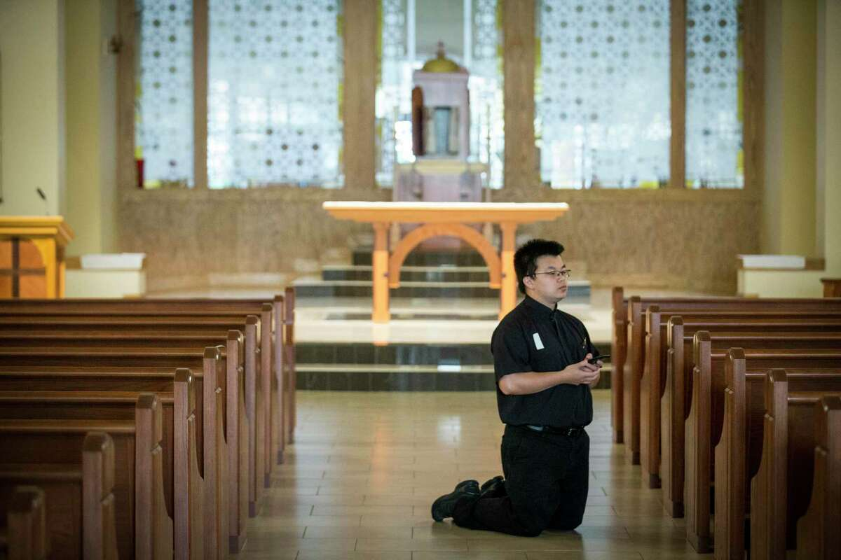 The Rev. Vincent Tran, parochial vicar, kneels as he participates in the Good Friday praying of the Stations of the Cross, Friday, April 10, 2020, at Christ the Redeemer Catholic Church in Houston. The coronavirus pandemic has shut down most religious services throughout the country and many churches are offering services through social media and video conferencing.
