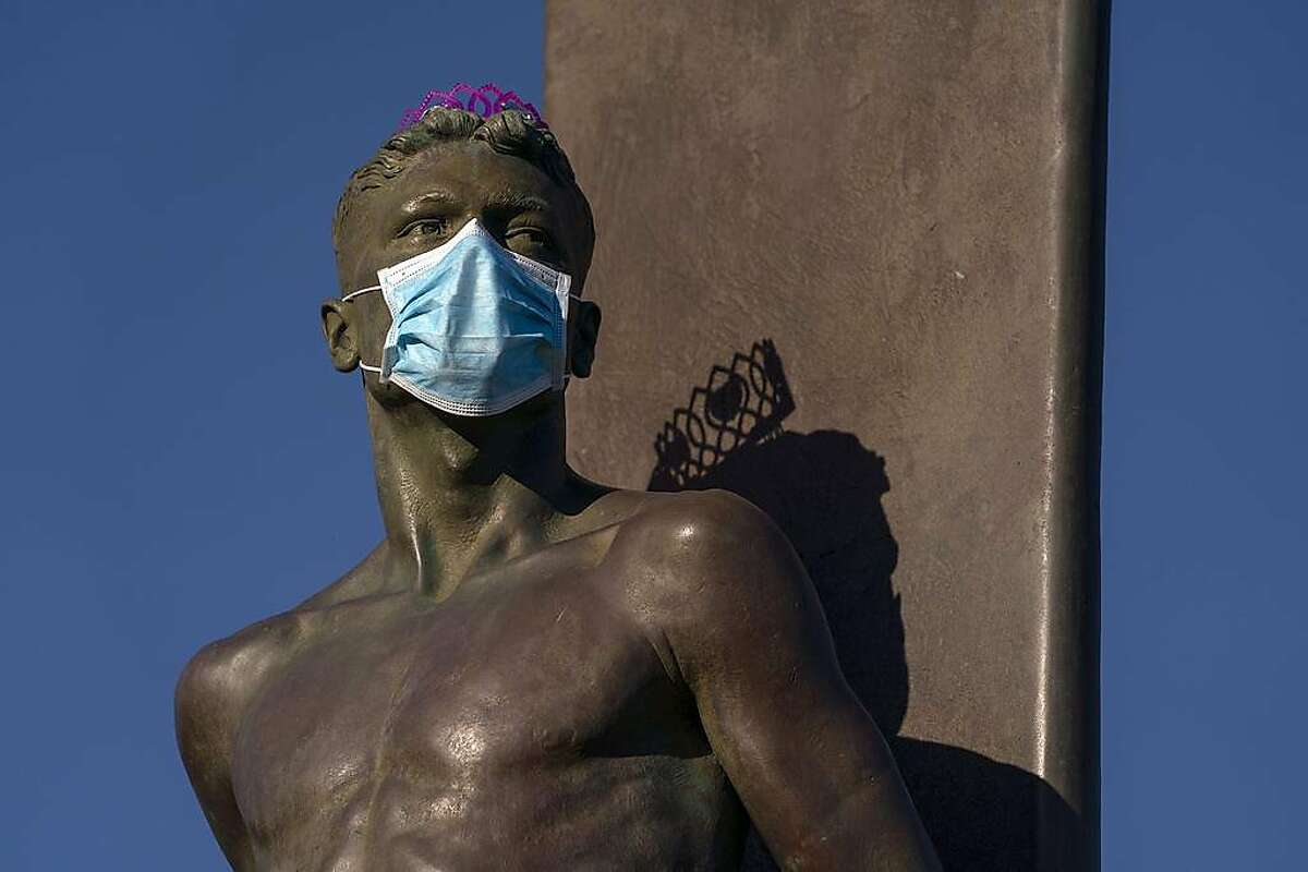 A medical mask covers the face of the statue honoring surfing by sculptors Brian Curtis and Thomas Marsh near Steamer Lane on W.Cliff Dr. on Wednesday, April 22, 2020 in Santa Cruz, Calif.