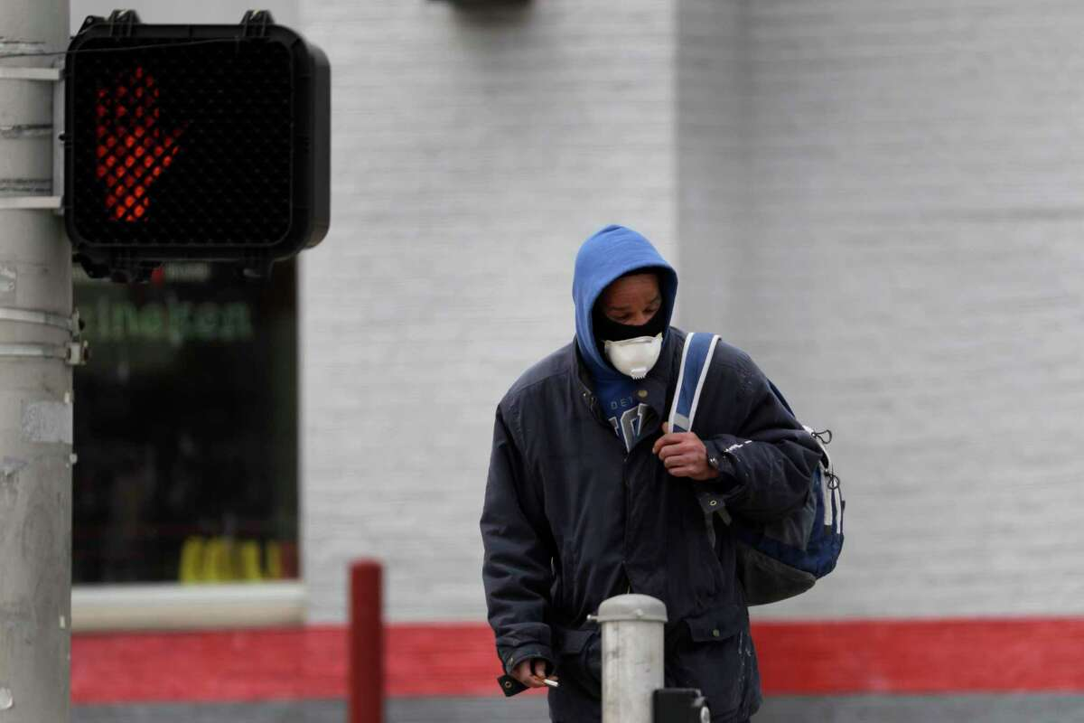 A man wears a protective mask as he waits to cross a street Monday, April 13, 2020, in St. Louis where parts of the city have been hit much harder than others by the coronavirus outbreak. Of people who are known to have died from from COVID-19 in St. Louis, black people are dying at a much higher rate than other populations. (AP Photo/Jeff Roberson)