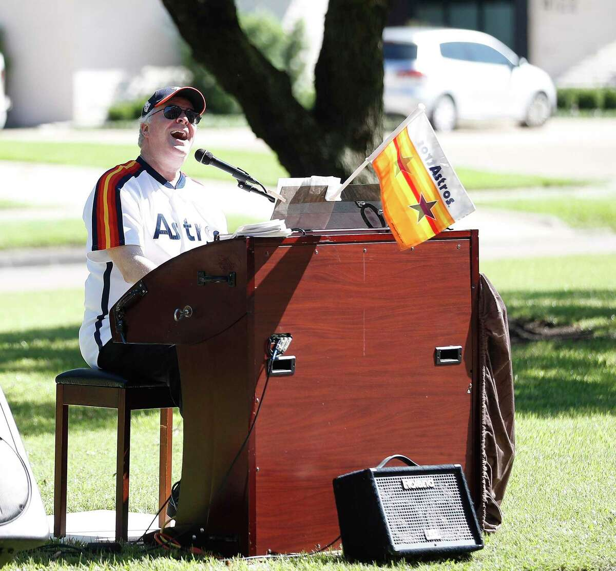 Former Astros organist, Jim Connors, sings and plays the organ as he presented his 7th Inning Stretch Show from the esplanade on North Braeswood Boulevard, to six floors of cooped-up, seniors at the Village of Meyerland, in Houston, Thursday, April 30, 2020.