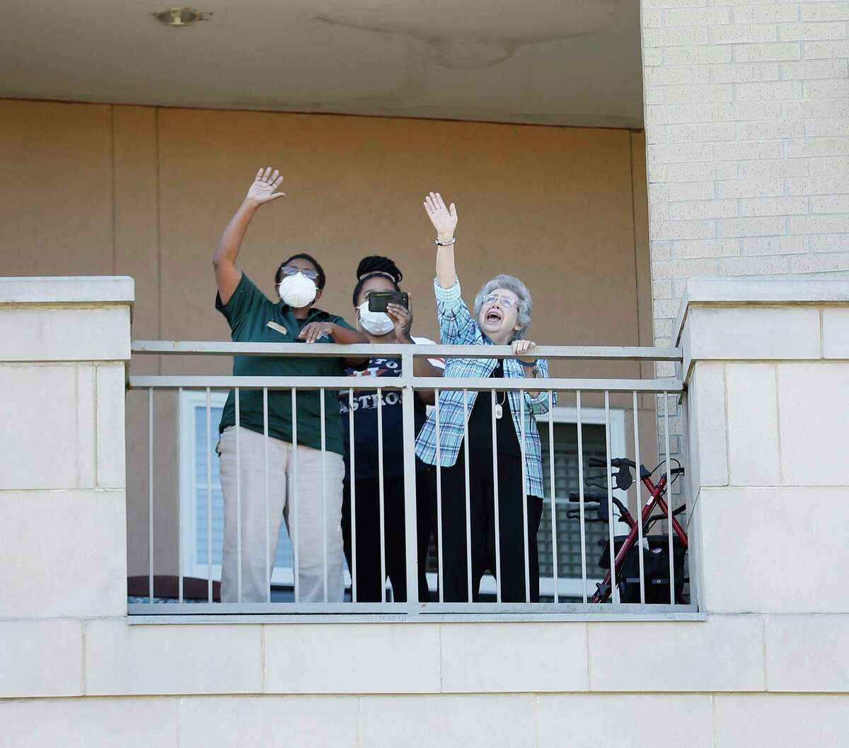 Residents and staff members stand on the balconies of Village of Meyerland as they listened to former Houston Astros organist, Jim Connors, presenting his 7th Inning Stretch Show from the esplanade on North Braeswood Boulevard.