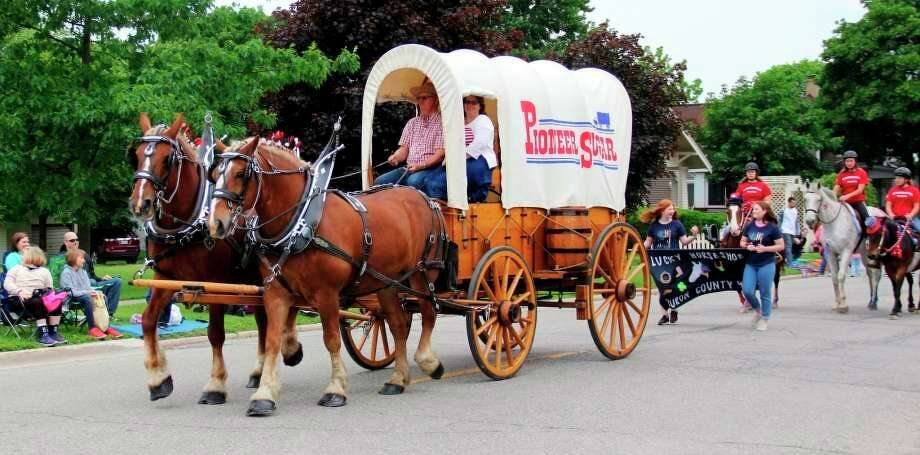 A covered wagon for Pioneer Sugar is pulled by horses during last year's Michigan Sugar Festival parade in Sebewaing. This year's festival has been canceled due to concerns surrounding the coronavirus outbreak. (Tribune File Photo)