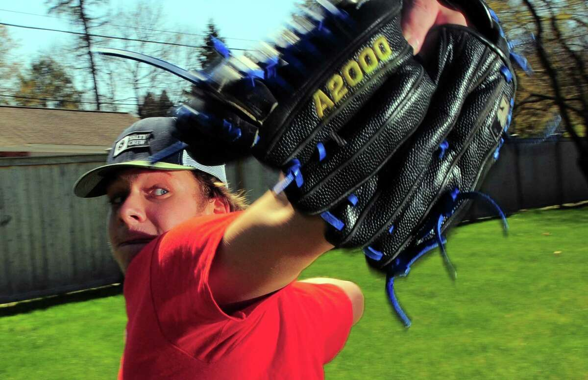 Chris Domizio, a pitcher on Ludlowe's baseball team, practices his pitching with his young brother Timmy, who plays as a catcher at Fairfield Prep, in their backyard in Fairfield, Conn., on Saturday Apr. 25, 2020.