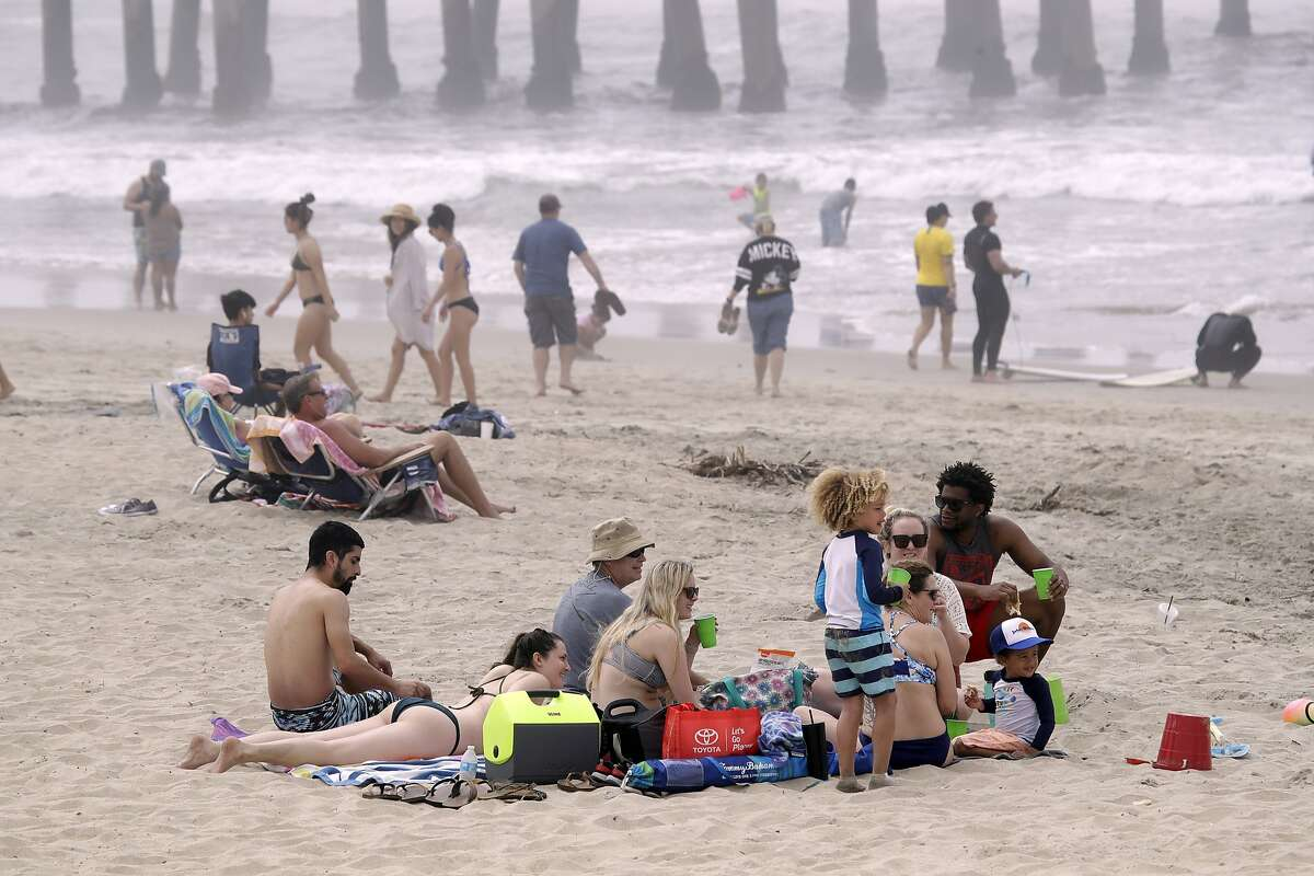 FILE - In this April 26, 2020, file photo, people sit on the beach in Huntington Beach, Calif. A memo sent to California police chiefs says Gov. Gavin Newsom will order all beaches and state parks closed starting Friday, May 1, to curb the spread of the coronavirus. The California Police Chiefs Association sent the bulletin to its members Wednesday evening. Association President Eric Nu�ez said it was sent to give chiefs time to plan ahead of Newsom's expected announcement Thursday. (AP Photo/Marcio Jose Sanchez, File)