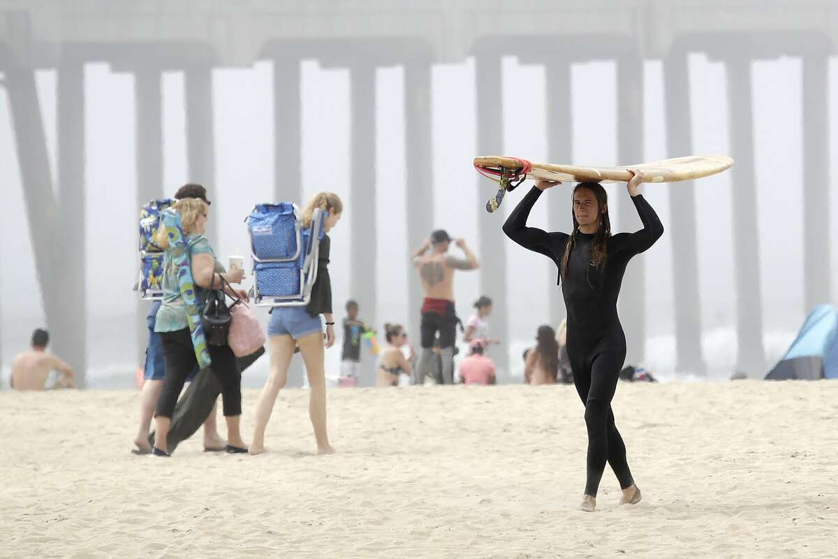 A surfer carries a board Sunday, April 26, 2020, in Huntington Beach, Calif. A lingering heat wave lured people to California beaches, rivers and trails again Sunday, prompting warnings from officials that defiance of stay-at-home orders could reverse progress and bring the coronavirus surging back. (AP Photo/Marcio Jose Sanchez)
