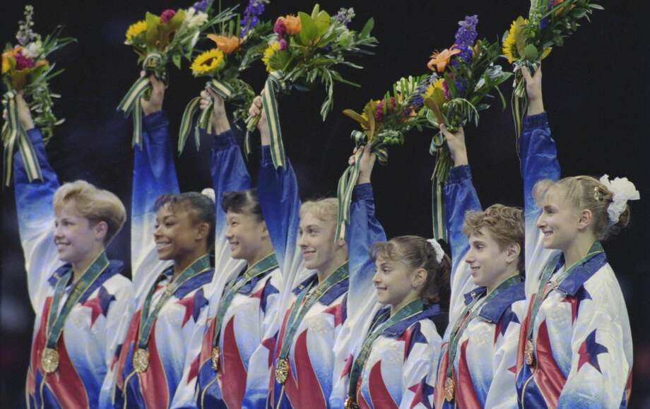 The U.S. gymnastics team (from left) Amanda Borden, Dominique Dawes, Amy Chow, Jaycie Phelps, Dominique Moceanu, Kerri Strug, and Shannon Miller celebrates their team gold medal on July 23, 1996 in Atlanta. Photo: Getty Images / 2017 Getty Images