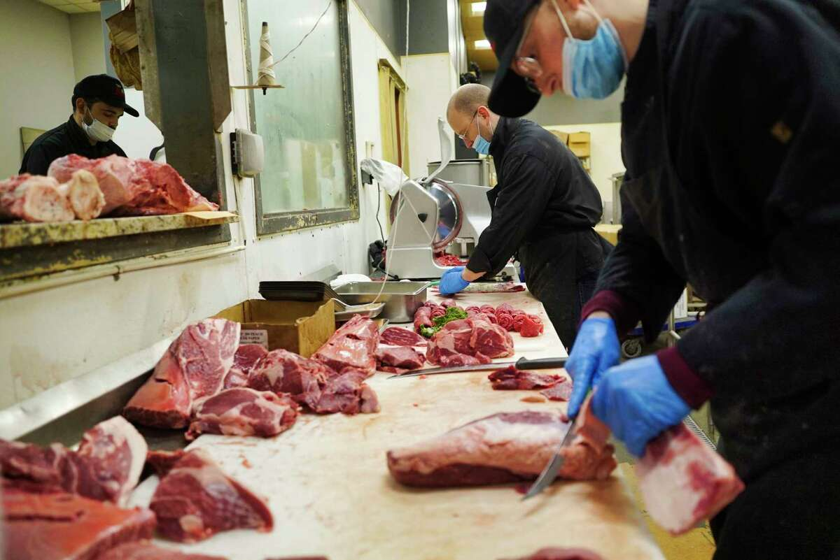 Brothers, Dylan MacVane, foreground, and David MacVane Jr., background center, who work for their father, David MacVane Sr., owner of Fred the Butcher, cut up meat at the store on Thursday, April 30, 2020, in Halfmoon, N.Y. (Paul Buckowski/Times Union)