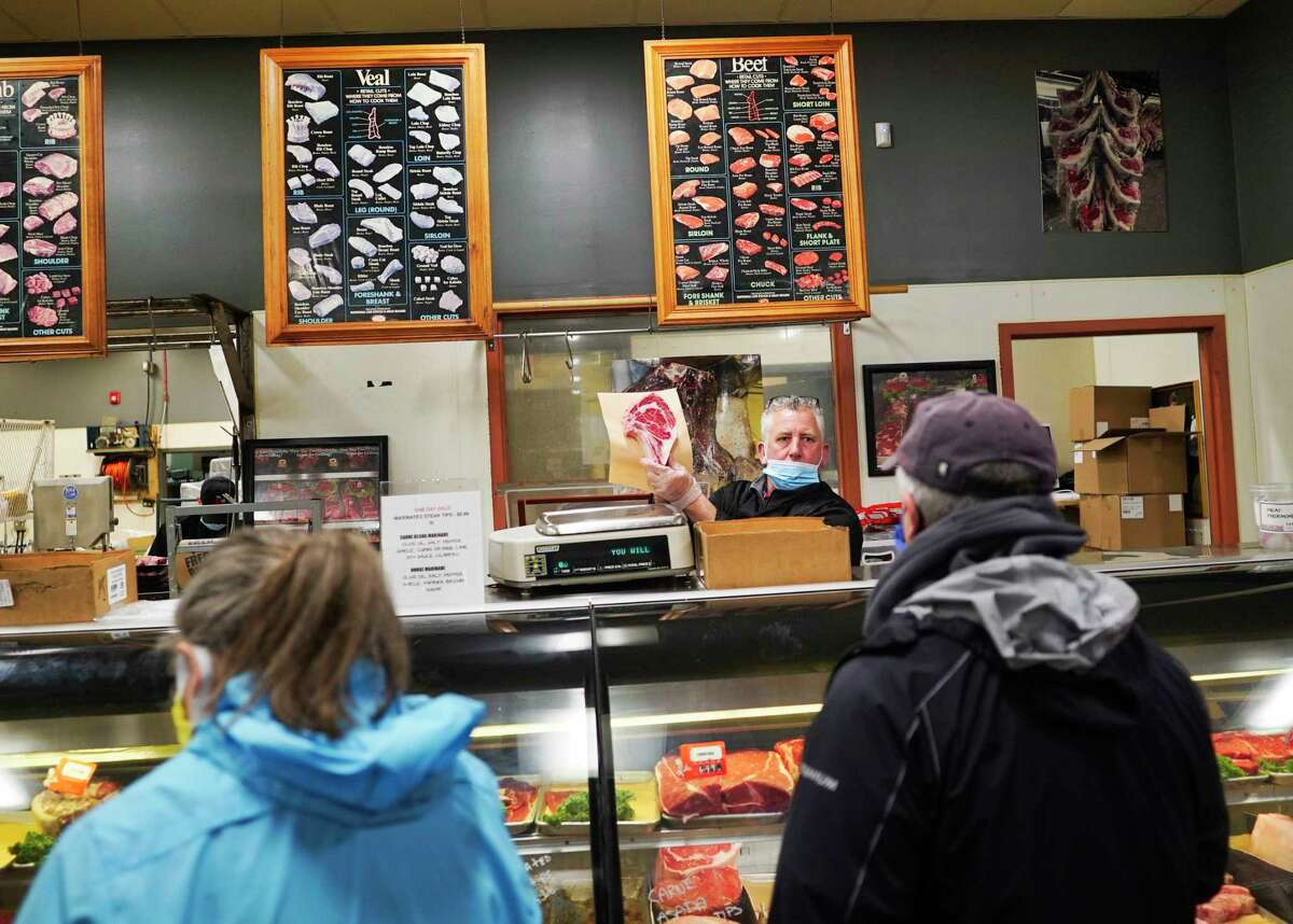David MacVane Sr., owner of Fred the Butcher, holds up a cut of meat for a customer to see at the store on Thursday, April 30, 2020, in Halfmoon, N.Y. (Paul Buckowski/Times Union)