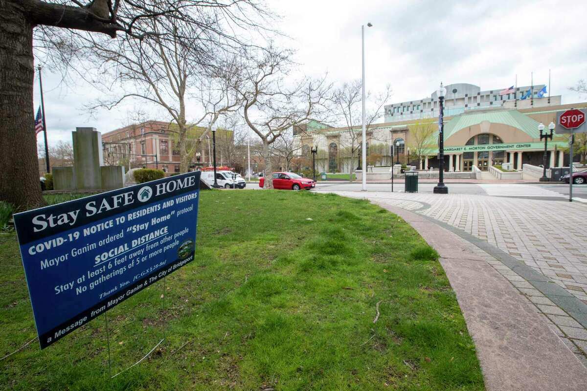 A sign announcing the mayor's stay at home order due to the coronavirus pandemic is seen on a lawn across the street from the Margaret E. Morton Government Center in downtown in Bridgeport, Conn, Monday, April 27, 2020. (AP Photo/Mary Altaffer)
