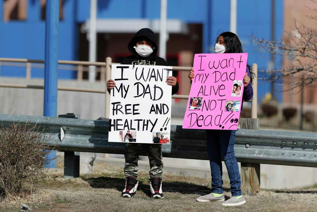 Protesters hold placards as members of the groups Abolish ICE Colorado, Sanctuary for All, American Friends Committee and Never Again Action take part in a car protest to call for the release of detained immigrants at the GEO Detention Center on April 3, 2020, in Aurora, Colo. (AP Photo/David Zalubowski)