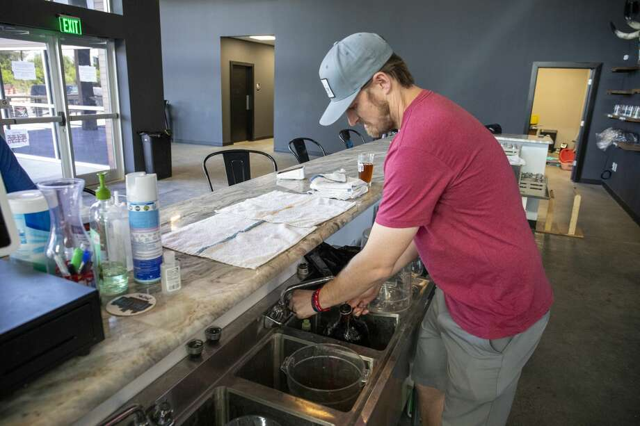 Co-founder Jeff Thomas fills growlers on Thursday, April 20, 2020 at Tall City Brewing Co. Photo: Jacy Lewis/Reporter Telegram