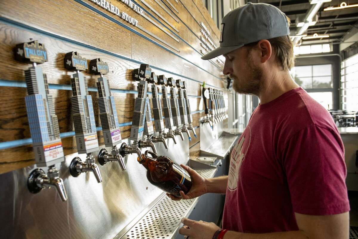 Co-founder Jeff Thomas fills growlers on Thursday, April 20, 2020 at Tall City Brewing Co.