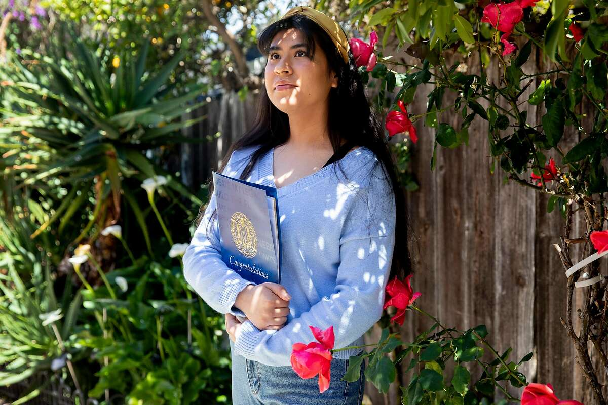 Viridiana Barreto poses with her UC Merced admissions packet while at her home in Oakland, Calif. Thursday, April 30, 2020. Barreto, a senior at Lighthouse Charter School in Oakland, changed her college choice from CSU Northridge to UC Merced in order to stay closer to home during the pandemic.