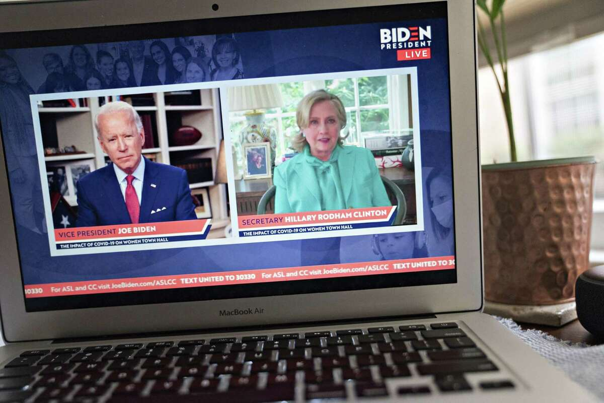 Hillary Clinton, former U.S. secretary of state, right, speaks as former Vice President Joe Biden, presumptive Democratic presidential nominee, listens during a virtual event seen on a laptop computer in Arlington, Virginia, U.S., on Tuesday, April 28, 2020. Clinton endorsed Biden today saying that she wishes he were in the White House to lead the country through the coronavirus pandemic. Photographer: Andrew Harrer/Bloomberg